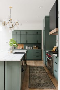 Green cabinetry in modern kitchen with warm vintage rug runner, black range hood with wood, modern cabin design - Studio McGee Design