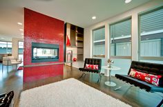 A stunning living room with a standout fireplace featuring modwalls® Brio® Clear Red mosaic glass tile. This beautiful space was created by the talented crew at Playhouse Design Group in Seattle, WA.