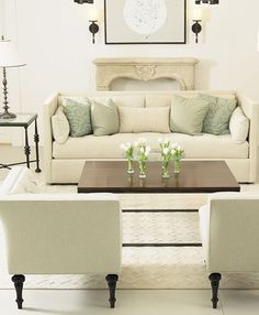 white linen couch and tufted corner chairs
