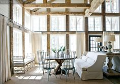 """The large main living space, defined by reclaimed wood beams that frame the windows overlooking Lake Martin, is divided into smaller, more intimate seating and dining areas by the towering fireplace. """"The homeowners wanted to have areas to do different activities and for different people in the family,"""" explains designer Paige Sumblin Schnell, principal of Tracery Interiors."""