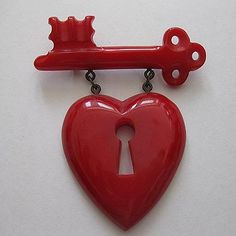 """Bakelite """"MacArthur Heart"""" and Key Pin. The pin was featured on the cover of """"Life"""" Magazine April 28, 1941 issue. During WWII, women would donate their precious metal to the war effort and buy plastic jewelry as a sign of patriotism and hope that their men would return home safely."""