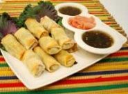 Egg Rolls With Green Chile and Chicken Recipe - Far East meets American West in this easy Tex Mex egg roll recipe. Dip these crispy egg rolls in the jalapeño-honey dipping sauce for an appetizer your guests will love.