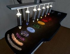 A crystal bed has 7 extremely clear and highly polished quartz crystals suspended approximately 12 inches above the client lying on a massage table. Each of the Quartzs crystals has been cut to a specific frequency. Each crystal is aligned above one of the seven  chakras. Coloured lights, chosen to match the chakra colours, radiate light and energy through the crystals to each respective chakra, and shine on and off in certain rhythms to cleanse, balance, and align your energies.