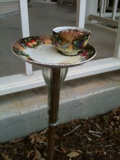 Tea cup and saucer bird feeder on upside down bud vase and wooden dowel