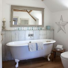 Use paint for a rustic effect The wide wood boards of this bathroom panelling are given a wash of pale paint (protect against splashes with a varnish) to tie in with a painted bath.