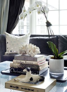 Update your coffee table top. Shop your home and look for decor that you can use on your table. Corral remotes on a pretty tray and display interesting books and a decorative accessory and voila.   orchid + books = great coffee table