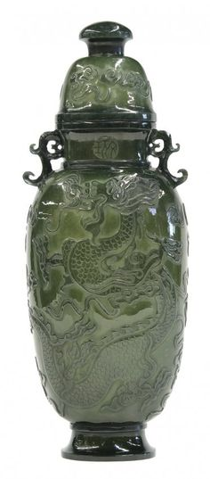 "Chinese spinach jade covered urn, of flattened ovoid form relief, carved with a pair of meandering dragons, the short neck with an apocryphal Qianlong mark flanked by scroll handles, the domed lid accented with clouds, 11.75""h"