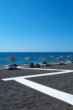 Black sand of Perivolos beach in Santorini.