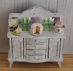 Miniature Shabby Chic Buffet/Chest With Mirror, Layer Cake With Pink Creamy Icing, Green Glass Stemware, And A Pretty Bouquet Of Flowers. $70.00, via Etsy.