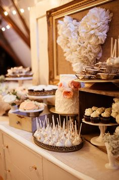 A romantic dessert table is covered in shades of white and pink.