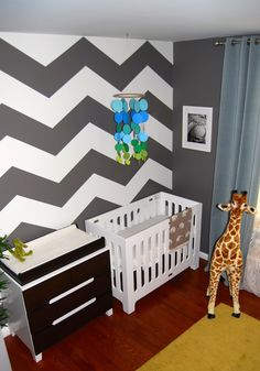 This #chevron accent wall makes a huge impact in this modern #nursery!