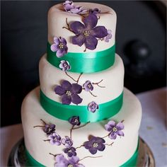 Beautiful three tiered, ivory, wedding cake. It was made from chocolate fruitcake, and wrapped with emerald green ribbon. Delicate purple flowers climbed the side of the cake.