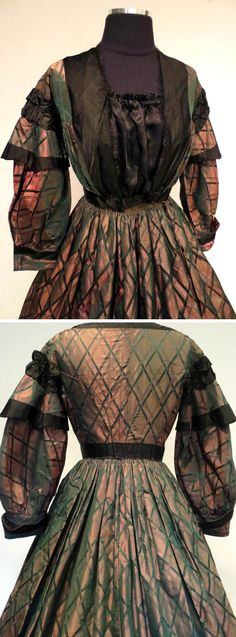 Circa 1860s changeable silk day dress in bronze, green, and purple, trimmed at bodice, waist, and sleeves with black silk. Neckline edged with black Chantilly lace. Double ruffle at shoulder with outer cap sleeve trimmed with black silk; long under-sleeve with cuff. Skirt is cartridge-pleated with hidden slanted pocket on right. Skirt and sleeves lined with brown glazed cotton; bodice lined with polished linen. Via coda2222/ebay.