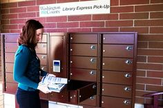 """""""A library worker shows how to check out books from a digitally locked cubby, in Hugo, Minn. Matt McLoone for The Wall Street Journal"""" -- Not surprisingly, these """"New Library Technologies [that] Dispense With Librarians"""" are controversial; click through to read more of the debate."""