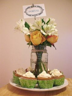 sample mason jar centerpiece on shabby chic white plate, raised table name sign on metal skewer, surrounded by cupcakes!