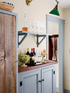 A wine cooler is hidden in the cupboard with the old wooden door in this kitchen.