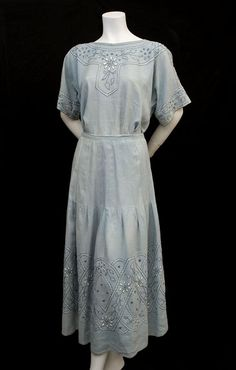 "Hand-embroidered linen blouse & skirt, c.1915 $850. Both pieces are hand embroidered with blue and white daisy-style flowers. The highly textured design is a pleasing arrangement of padded satin stitch, French knots, and cross stitch. The blouse and skirt can be worn together as a dress or as separates. The blouse measures: 40"" bust, 36"" waist, and 18"" from shoulder to hem.  The skirt measures: 30"" waist, 42"" hip, and 35"" length."