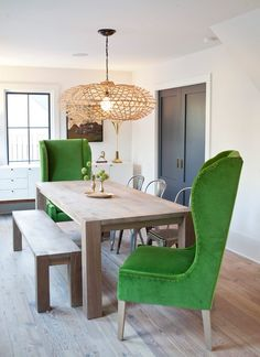 earthy and modern farmhouse dining room with unique details: bright green velvet club chairs, wood bench, dining chairs