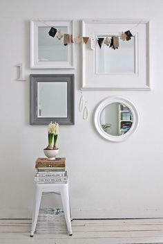 Multiple Mirrors on a Wall, #white square mirrors, #stack of books and magazines