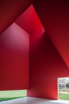 Bright red walls contrast with vivid green lawns at this art and culture centre