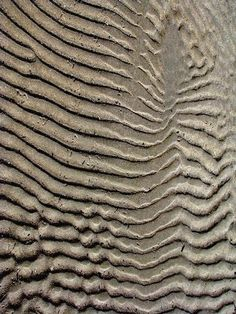 texture- this shows texture by making the sand in big bulges. it also could be seen as ripples through water flowing into the middle of the artwork. it also gives a bit of movement into the center.