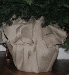 """Burlap stand cover I like this idea better than a skirt! I might use red with white trim to mimic Santa's bag Tie together w/ black ribbon or felt and a""""buckle"""""""