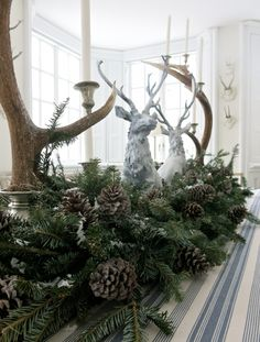 Reindeer figureines with greenery, pinecones and anters -  by Carolyne Roehm