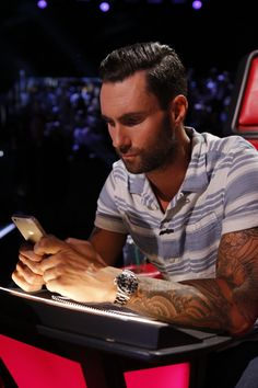 """Hey, no texting and judging. Adam Levine of Maroon 5 takes care of some business during a taping of """"The Voice"""" on April 29 in Los Angeles"""