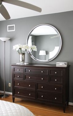 Grey walls with brown furniture. I love the big round mirror