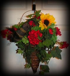 "Vine cone shaped pocket with metal   support.....has Geraniums, Greenery, sunflower and Mr. Bumblebee.....So   pretty.....It is 20"" in height....$26.99  http://www.primitivehomedecorandmore.com/floral-wreaths.html"