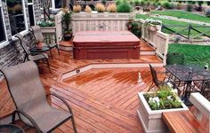 Redwood deck with multiple levels and built-in seating. White accents add interest as well. Designed by @DeckTec Outdoor Design