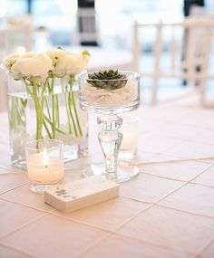 Elegant centerpiece  Feminine lines and curves, clean and simple florals in crisp whites, along with sand tones and aqua. A beautiful centerpiece in glass vases, filled with white crushed glass and a green succulent. Created by Carissa Jones-Jowett of JL DESIGNS.