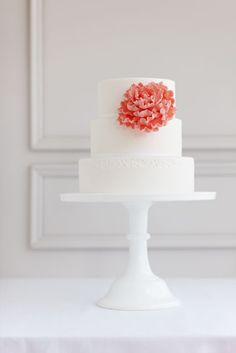 Simple white cake with a large coral flower.