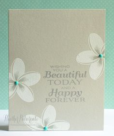 Stamp dark grey sentiment on light grey card base, stamp flowers with Versamark and then white embossing powder. Add enamel dots for accents. (But pearls or rhinestones would look good too.) From MFT stamp blog.