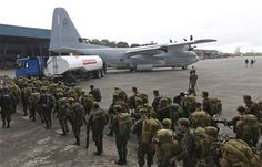 Philippine soldiers walk near a military C-130 plane as they prepare to go to Tacloban city, at the Villamor Airbase, in Manila, Philippines on Tuesday, Nov. 12, 2013. Four days after Typhoon Haiyan struck the eastern Philippines, only a trickle of assistance has made it to affected communities. Authorities said at least 9.7 million people in 41 provinces were affected by the devastating typhoon. (AP Photo/Vincent Yu)