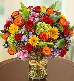 Garden of Grandeur™ for Fall: Vibrant red & bi-color #roses, sunflowers and purple monte casino with unique dried lotus pods and folded aspidistra leaves in a chic glass cylinder vase.