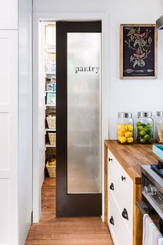 A frosted-glass pocket door closes off this pantry without obstructing floor space. And scraps of butcher block along the sides of the range-wall cabinets create a waterfall effect. | Photo: Andrea Rugg | thisoldhouse.com