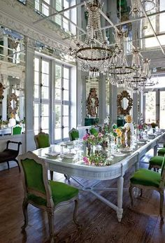 The table in the formal dining-room was once in a Paris library. It is now painted and mirrored, surrounded by antique chairs covered in green mohair. From the mirrored ceiling hang four identical chandeliers, a rare find from a church.  Picture: PAUL RAESIDE