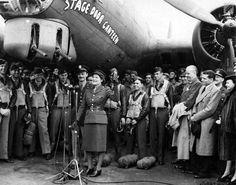 """Mary Churchill, daughter of Prime Minister Winston Churchill, is just about to let loose a bottle of Coca Cola on the nose of """"Stage Door Canteen"""", Boeing B-17 Flying Fortress in the official christening ceremony in the presence of high ranking officers, members of crew, and visiting stars of stage and screen.   At far right: Laurence Olivier and Vivian Leigh."""