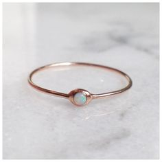 A droplet of opal set in a whisper-thin band of gold.