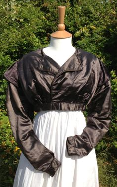 c1820 brown silk spencer. The silk is a chocolate brown, but can take on a purple sheen. High front waist, but lower at the back. Double-piped revers at the front, but no actual collar. Double-piped sleeve caps. Cuffs single piped.