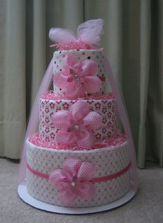 I like the use of the netting bunched up and around the 'cake' to help hold it together and also give it a finished look. baby girl diaper cakes | ... Baby Girl Diaper Cake for Baby Shower Centerpiece and New Baby Gift