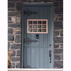 Cottage Dutch Door  A tongue-and-groove Dutch door, painted an earthy shade of teal, is a complement to a stone cottage—complete with vine-like scrolled strap hinges.