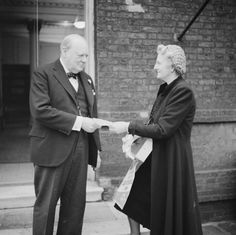 The Prime Minister Winston Churchill purchases a British Red Cross 'Aid to Russia' flag from his wife Clementine, on 9 December 1941.