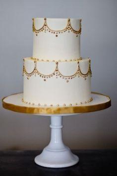 Gold icing mimics twinkle lights on this wedding cake. #white #gold #weddingcake