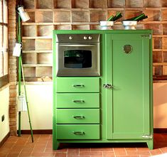 Green vintage kitchen unit includes refrigerator, oven, and storage drawers.