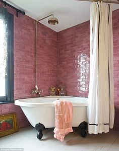 Bathroom with pink subway tile and black painted window trim - Claw foot bathtub - Wood painted floors