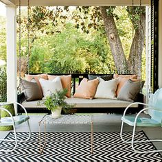 Front Porch    Mix old and new.   Add instant character to a new porch with a pair of vintage metal chairs painted with two coats of an exterior oil-based color.    Repeat exterior colors in furniture.   A black-painted porch swing, piled with various pillows, looks great with the shutters.