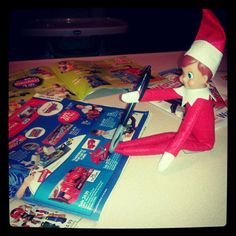 """Elf on The Shelf Idea #1: """"Elvin"""" the Elf making notes from Connor's wish books. #elfontheshelf"""
