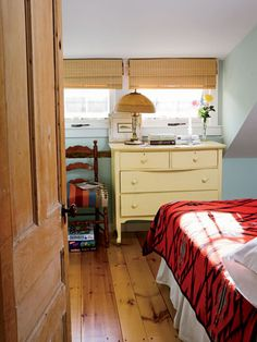 Red accents look right at home with a yellow dresser and blue walls.